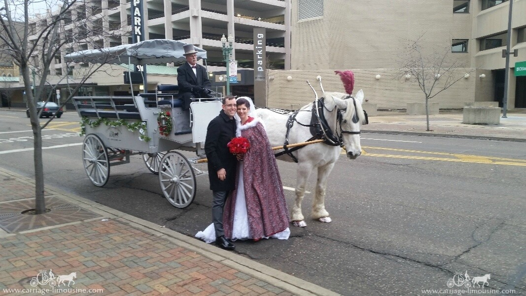 The bride and groom posing with the Limousine Carriage in Canton, OH